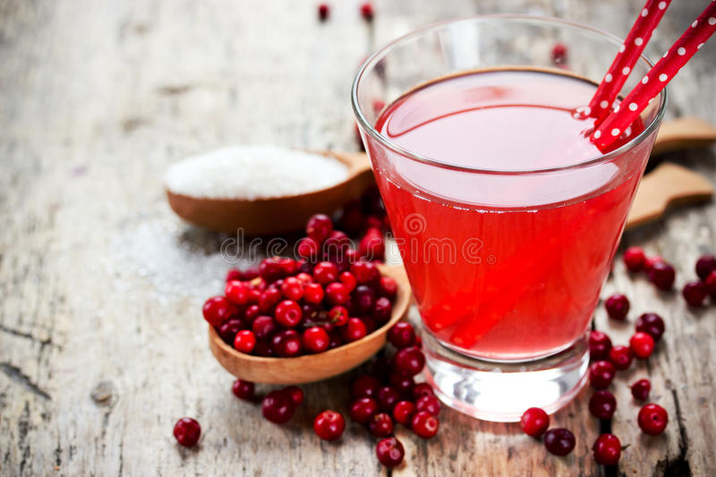 Glasses of fresh cranberry drink on wooden background. Red bilberry, whortleberry, huckleberry, cowberry, foxberry, lingberry, li stock photo