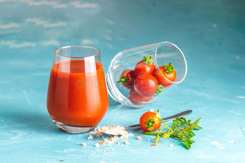 Glasses of fresh delicious jummy red tomato juice and fresh raw tomatoes with pink salt in spoon on light concrete surface. Close royalty free stock photos