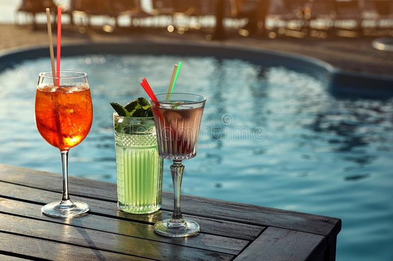 Glasses of fresh summer cocktails on wooden table near swimming pool. Space for text. Glasses of fresh summer cocktails on wooden table near swimming pool stock image