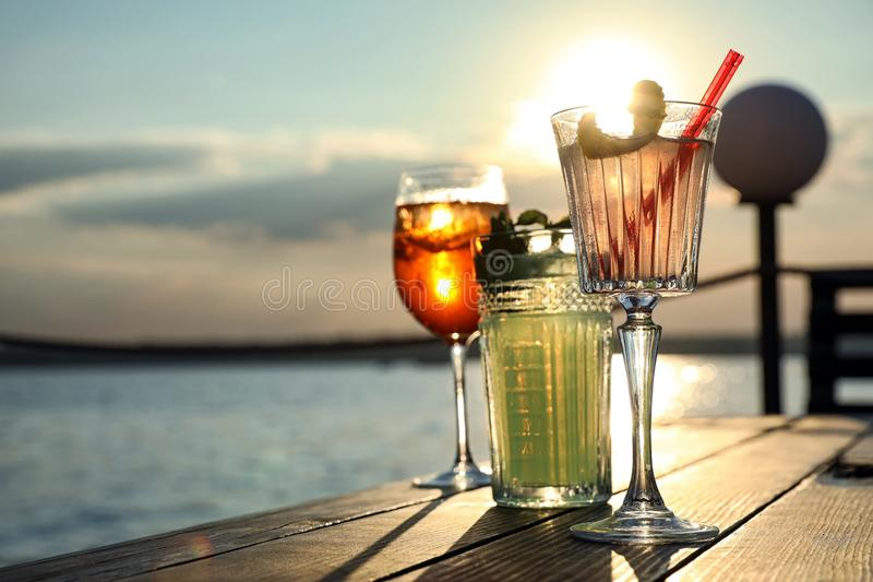 Glasses of fresh summer cocktails on wooden table at sunset, low angle view. Space for text. Glasses of fresh summer cocktails on wooden table outdoors at sunset royalty free stock photo