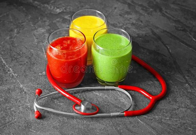 Glasses with fresh tasty smoothies and stethoscope on table. Health care concept royalty free stock photos