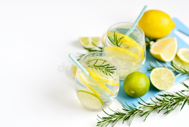 Glasses with Fresh Water Rosemary Lemon Lime Fruits stock photography