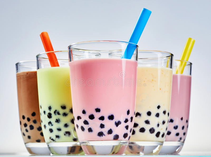 Glasses of fruity bubble tea with tapioca balls. Glasses of fruity bubble or boba Asian tea with tapioca balls or pearls and milk served with wide straws in royalty free stock photography
