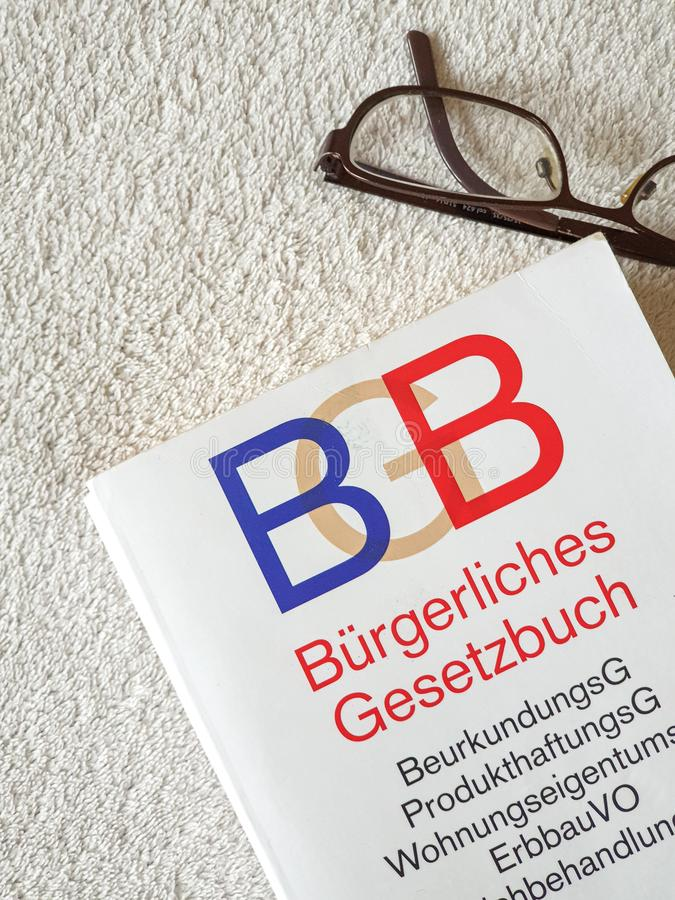 Glasses and a german BGB book. Glasses, open, book, reading, education, page, paper, dictionary, literature, library, business, study, spectacles, white, text royalty free stock photography
