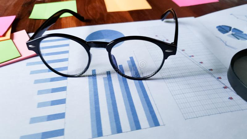 glasses on graph paper on  wooden desktop in modern office with accessories,Copy space for your text stock photo