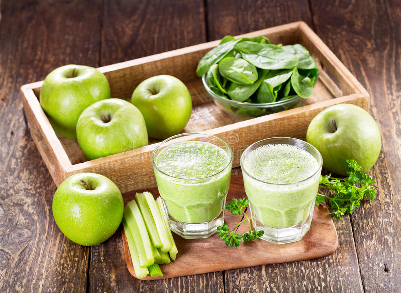 Glasses of green juice with apple, celery and spinach royalty free stock photography