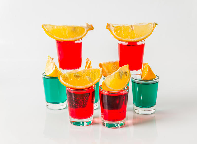 Glasses with green and red kamikaze, glamorous drinks, mixed drink poured into shot glasses. Party set royalty free stock images