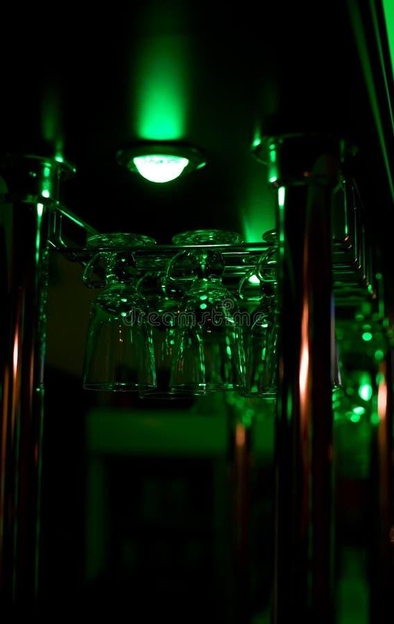 Glasses hang above a bar royalty free stock photography