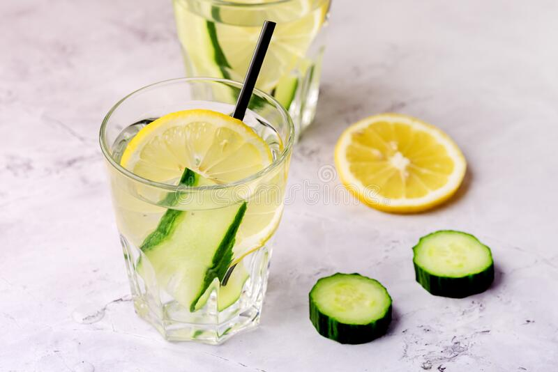 Glasses of Healthy Detox Water with Lemon and Cucumbers Diet Drink Straw Horizontal Above.  royalty free stock image