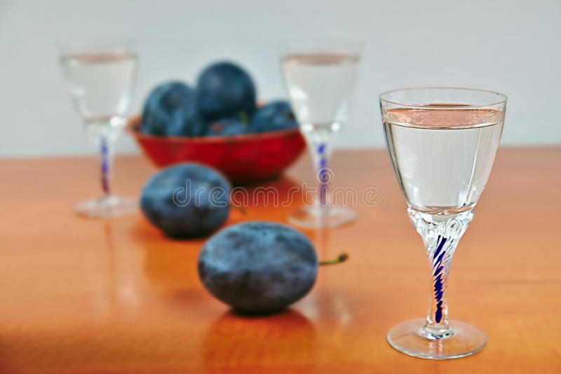 Glasses of homemade plum brandy with plums royalty free stock image