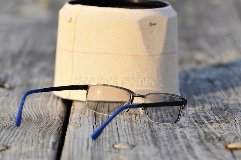 Closeup of hood and glasses on a wood desk. Glasses and hood in fall are placed on a wood desk stock photos