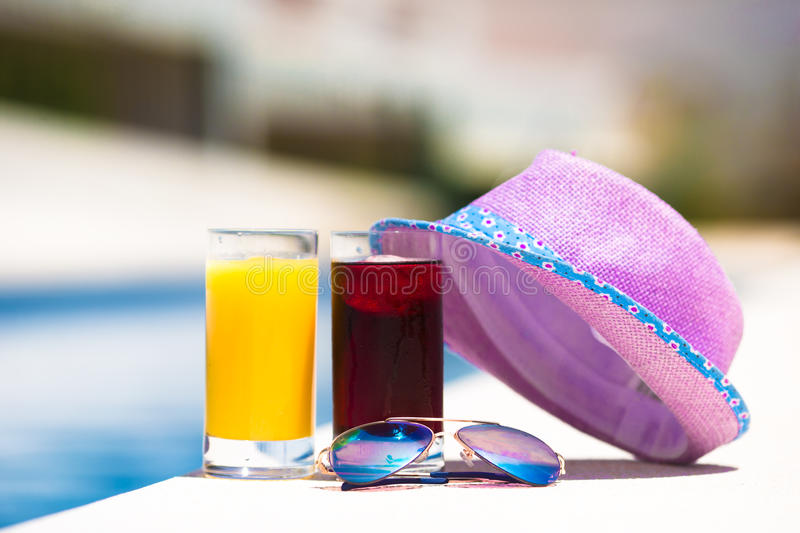 Glasses of juice, straw hat, sunglasses on summer. Sunglasses, orange juice, and straw white hat on summer vacation near pool stock photos