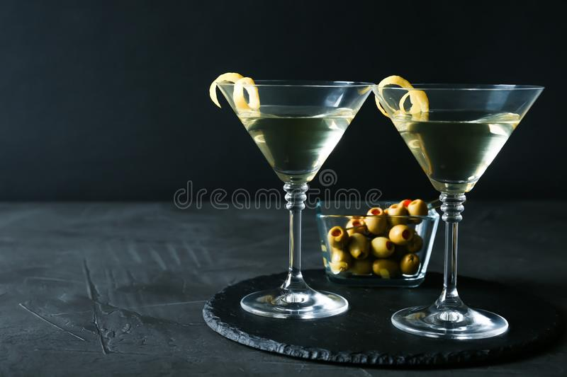 Glasses of Lemon Drop Martini cocktail with zest on grey table against black background stock images