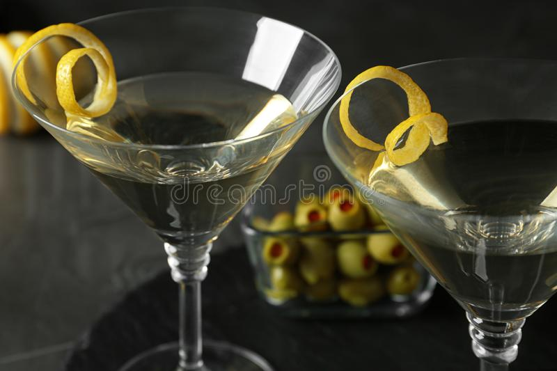 Glasses of Lemon Drop Martini cocktail with zest on grey table stock photos