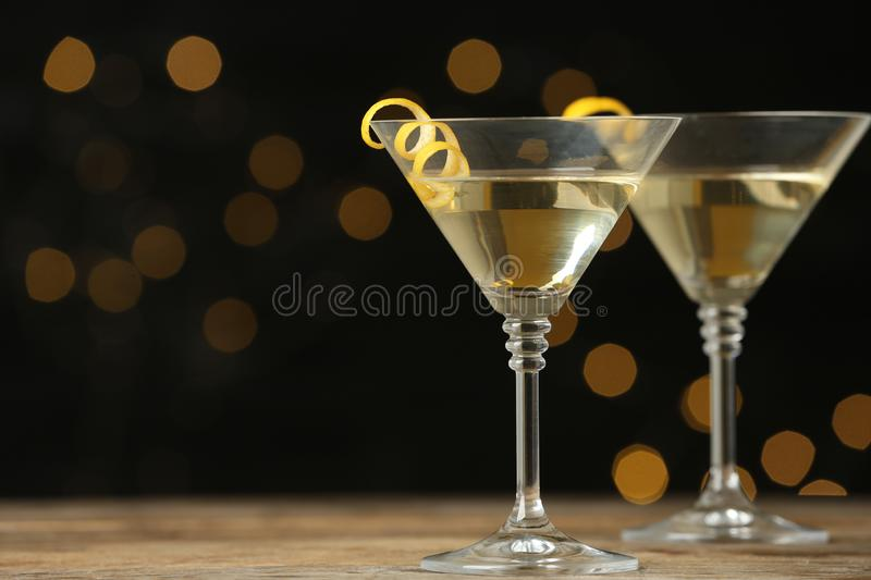 Glasses of Lemon Drop Martini cocktail with zest on wooden table against blurred background. Space for text stock photos