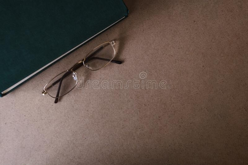 Glasses lie near the green book on the wooden background. The concept of reading and education. Top view, copy space royalty free stock image