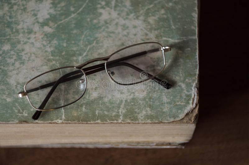 Glasses lie on an old book with torn edges with a shabby cover. The concept of learning, reading and education. Top view.  stock photos