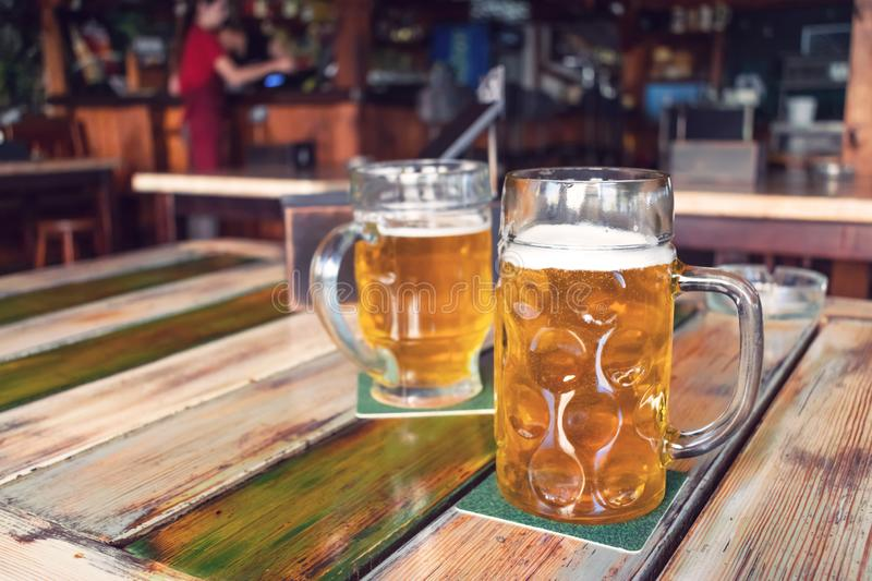 Glasses of light beer on pub background. Pint glass of golden beer with snacks stock image