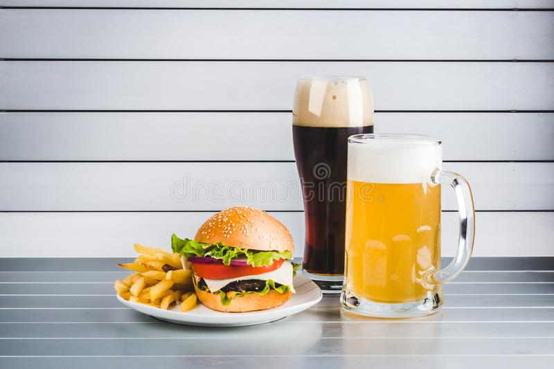 Glasses of light and dark beer with cheeseburger and French fries on aluminum panels stock photography