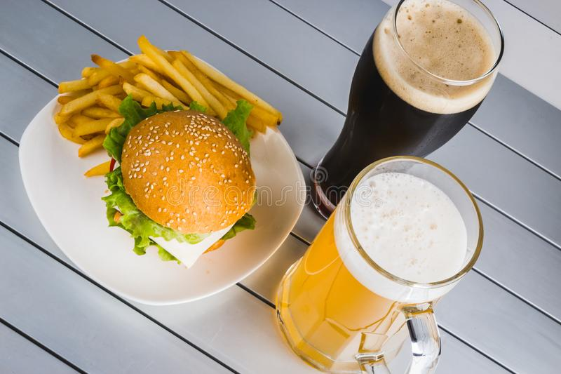Glasses of light and dark beer with cheeseburger and French fries on aluminum panels royalty free stock images