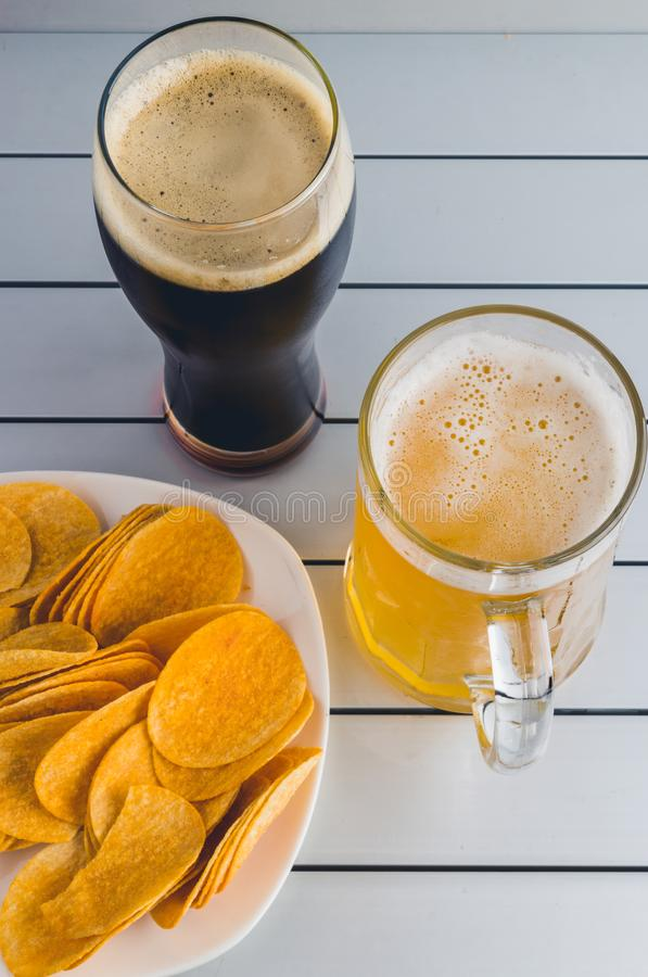 Glasses of light and dark beer with chips on aluminum panels royalty free stock photo