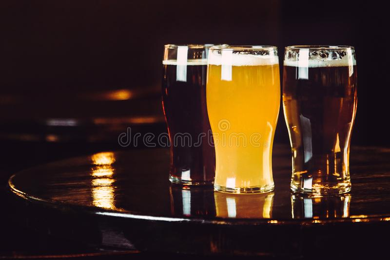 Glasses of light and dark beer on a pub background royalty free stock photography