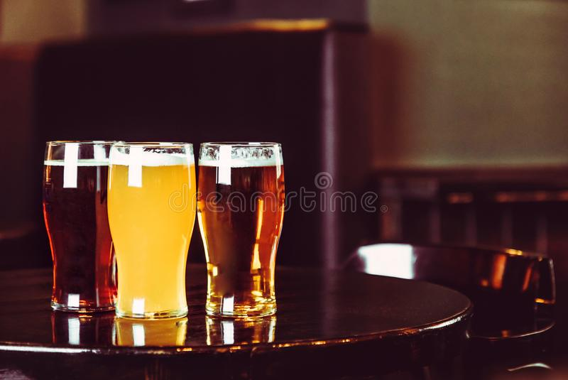 Glasses of light and dark beer on a pub background royalty free stock image