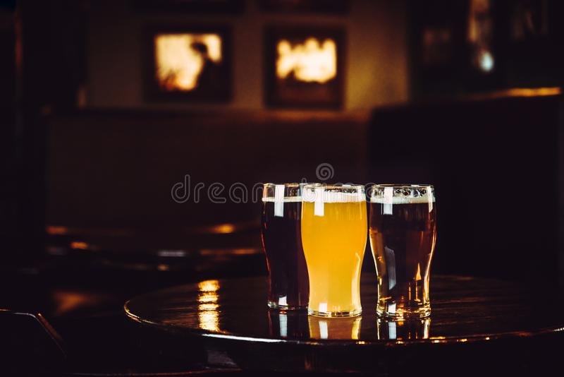 Glasses of light and dark beer on a pub background royalty free stock images
