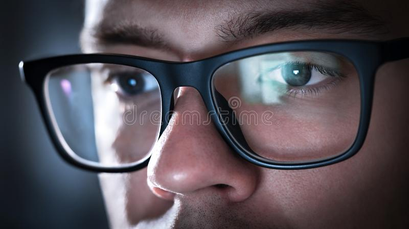 Glasses with light reflected from computer or smartphone screen. Thoughtful business man or focused student working late at night. Coder, programmer or geek stock photos