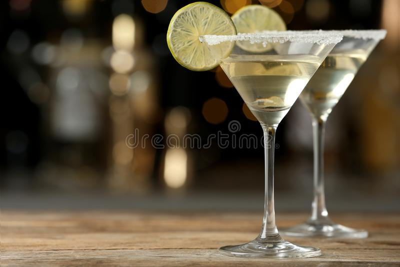 Glasses of Lime Drop Martini cocktail on wooden table against blurred background stock photo