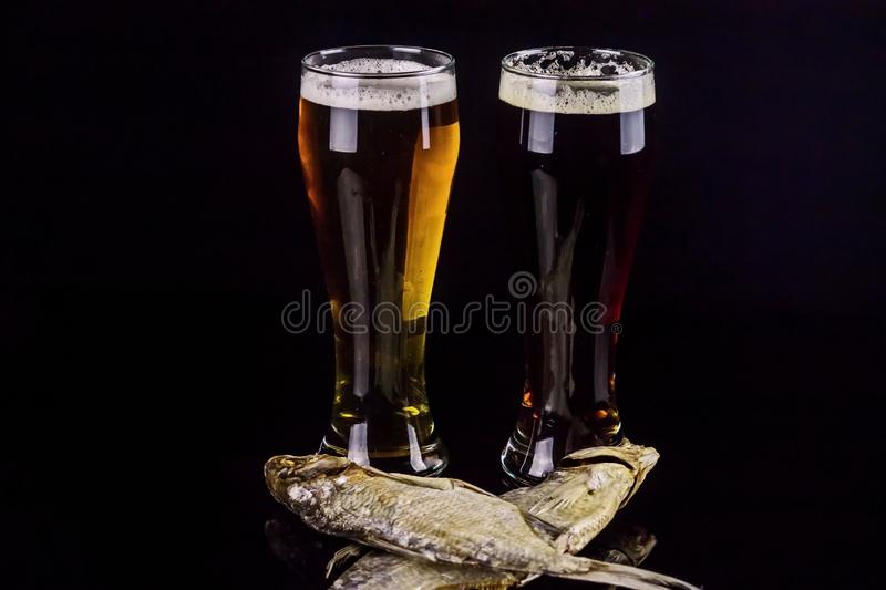 Glasses 0.5 liter of dark and light beer with dried fish close-up on a black background stock photo