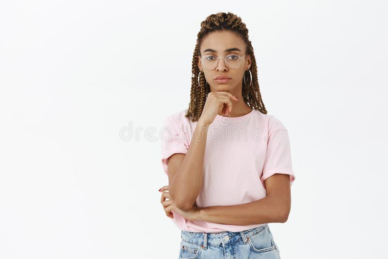 Glasses make me smarter. Portrait of serious-looking clever and thoughtful charming dark-skinned girl with dreads and royalty free stock photography