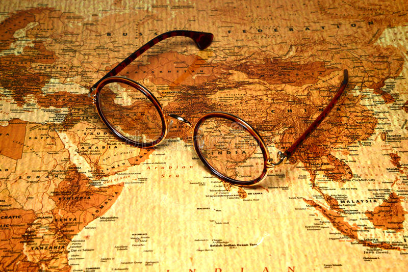 Glasses on a map of a world - India. Photo of glasses on a map of a world, antique style. Focus on India. May be used as illustration for traveling theme royalty free stock images