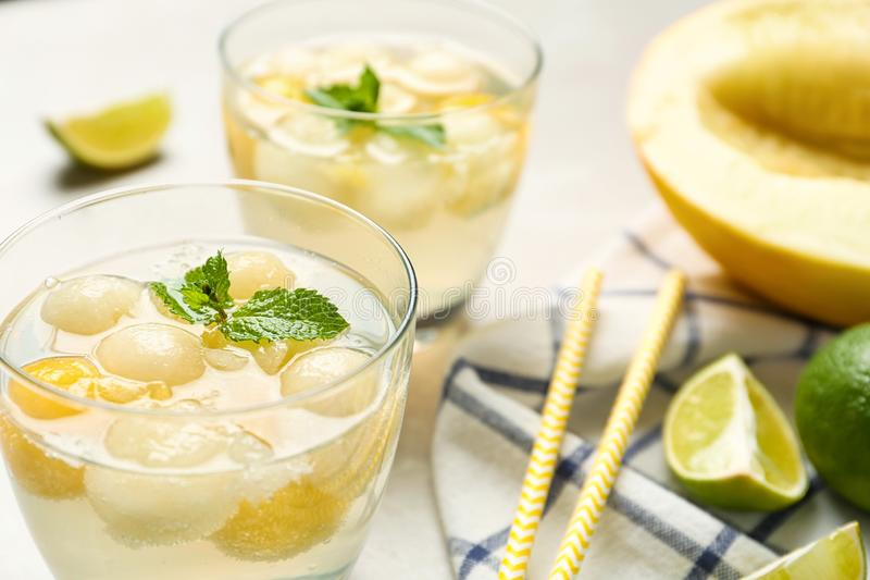 Glasses of melon ball cocktail with mint on table royalty free stock images