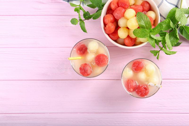 Glasses of melon and watermelon ball cocktail on pink wooden table. Space for text royalty free stock photos