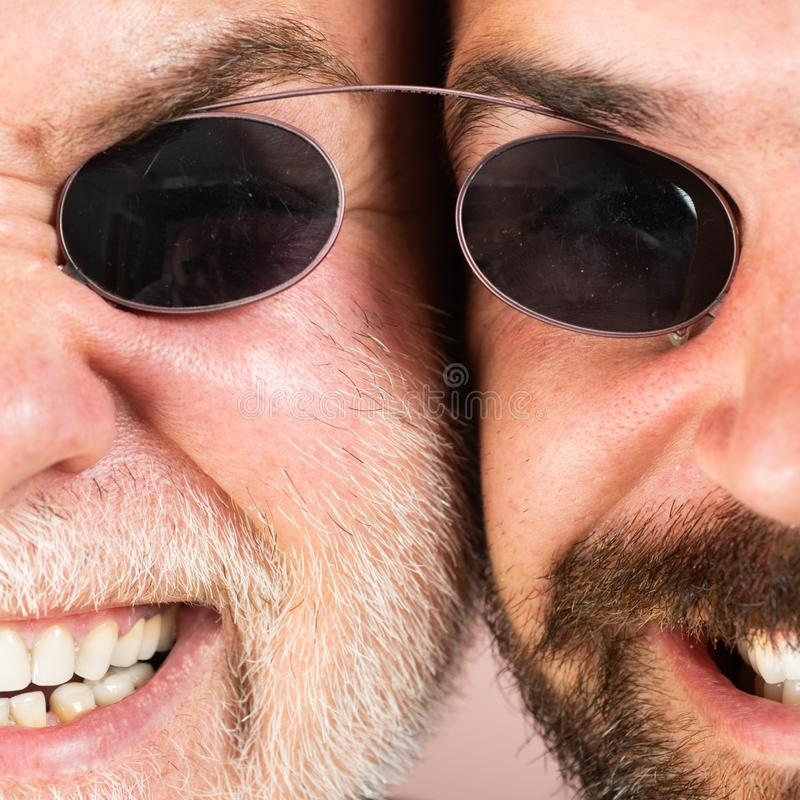 Glasses for men. Two Beardeds middle-aged mans wearing glasses looking at camera with a serious expression. Glasses. Concept. Senior men with son stock photos