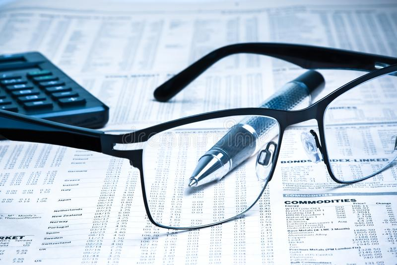 Glasses near calculator with pen on financial newspaper royalty free stock image