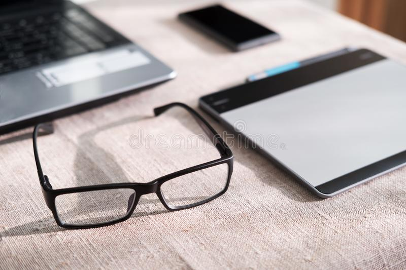 Glasses near the computer on the Desk, phone and tablet operating environment. Corporate royalty free stock image