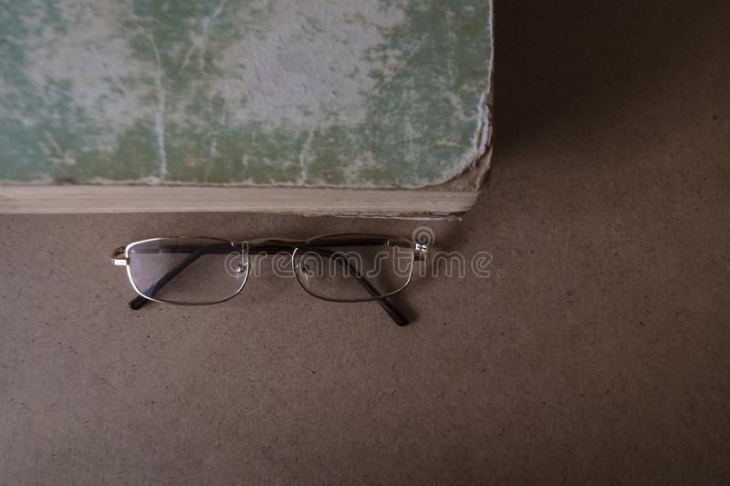 Glasses near the old book with torn edges and shabby cover. The concept of reading and education. Top view, copy space. Glasses lie near the old book with torn stock images