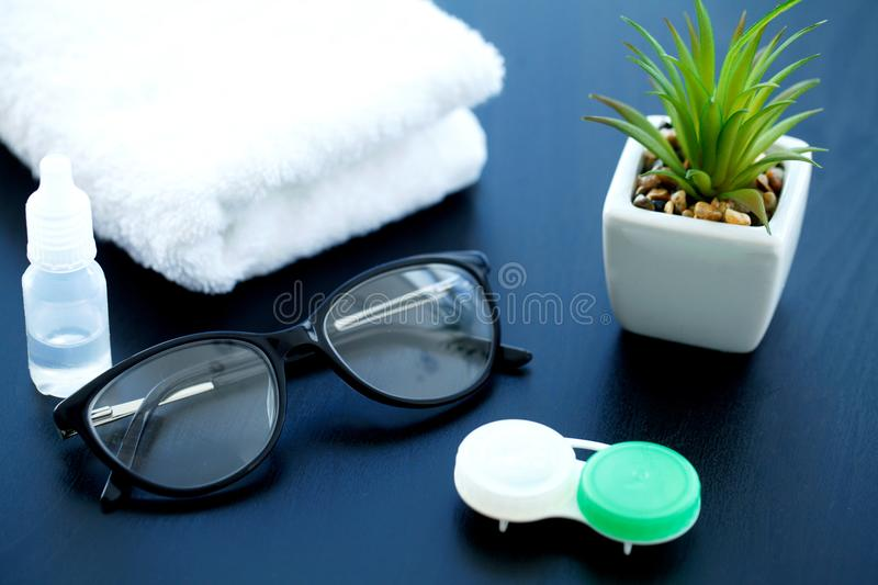 Glasses and objects for cleaning and storing contact lenses, to. Improve vision, on a black background stock photography