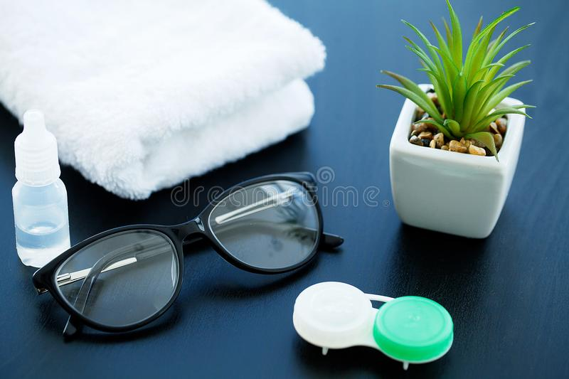 Glasses and objects for cleaning and storing contact lenses, to. Improve vision, on a black background royalty free stock photos