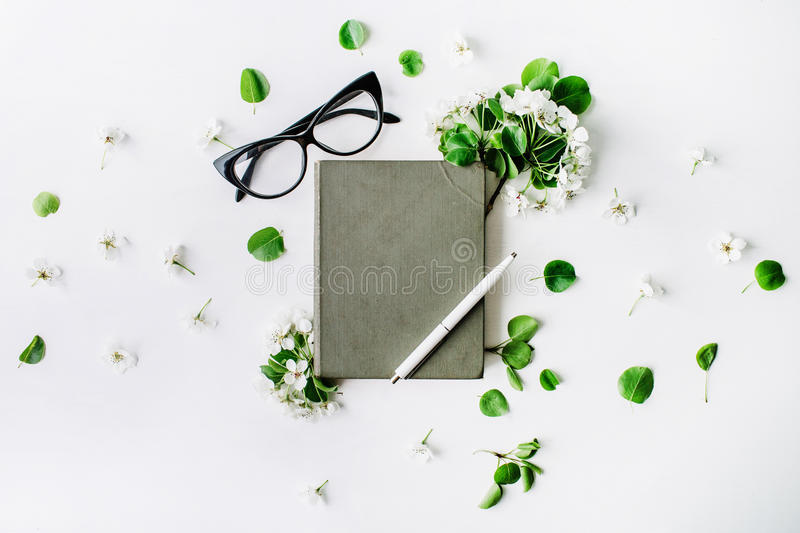 Glasses, old book, pen and branches with leaves and flowers on white background stock image