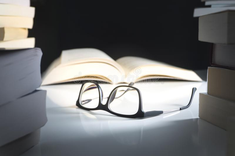 Glasses and open book on table surrounded by literature. Education, learning and reading concept stock photography