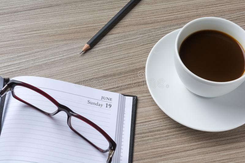 Glasses over a personal organizer and a cup of coffee on a desk royalty free stock photography