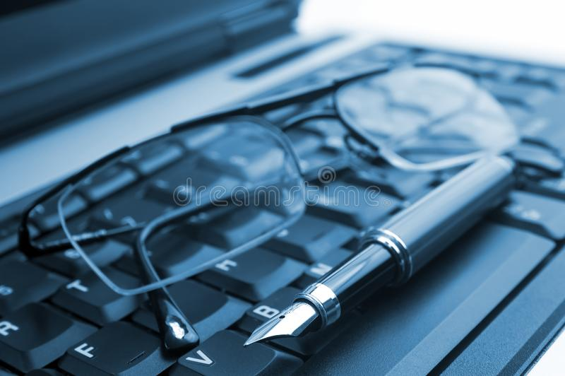 Glasses and pen on laptop stock image