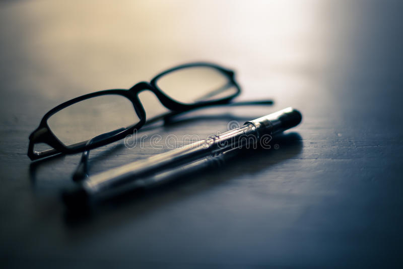Glasses and pen on a table royalty free stock photos