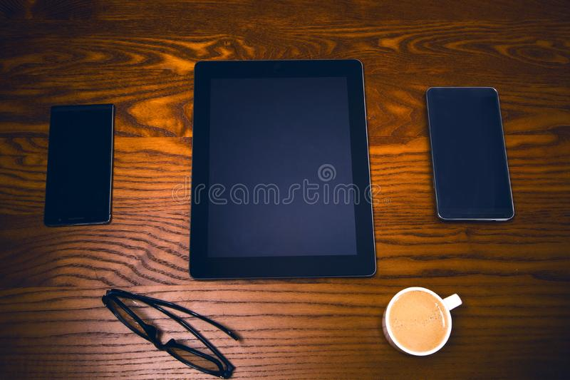 Glasses with pen and tablet on a wooden natural table. Home office. Concept of work in a office and accessories royalty free stock photos