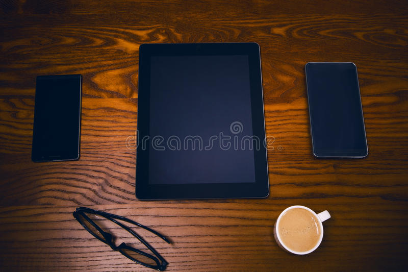 Glasses with pen and tablet on a wooden natural table. Home office. Concept of work in a office and accessories royalty free stock photo