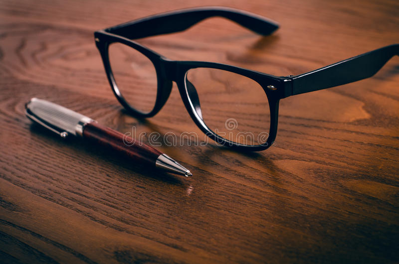 Glasses with pen and tablet on a wooden natural table. Home office. Concept of work in a office and accessories stock images