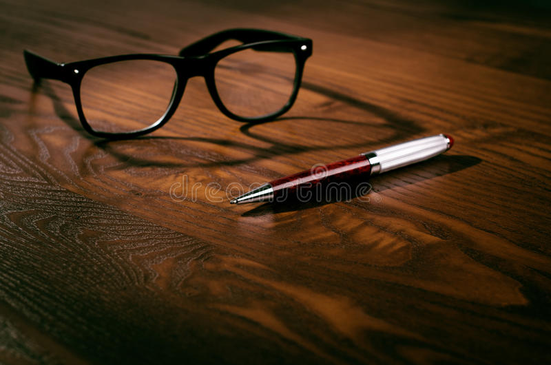 Glasses with pen and tablet on a wooden natural table. Home office. Concept of work in a office and accessories stock photography